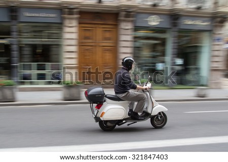 VALENCIA, SPAIN - SEPTEMBER 28, 2015: A businessman on a scooter in the city center of Valencia. Due to the economic crisis, scooter sales in Europe have declined 20 percent in the year 2014. - stock photo