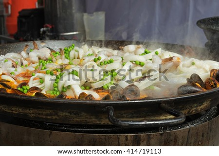Valencian rice dish, seafood paella - sliced squid, shrimp, mussel, green beans being cooked in a large shallow pan  - stock photo