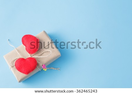 Valentine. A paper parcel wrapped tied. A red heart on a gift box wrapped with paper kraft - stock photo