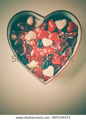 Valentine box with heart-shaped candies and sprinkles with copy space - stock photo