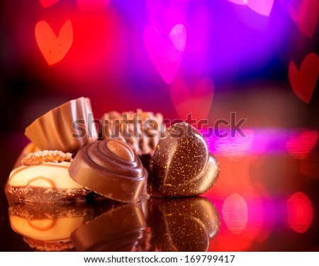 Valentine Chocolates. Assorted Chocolate Candies. Chocolate Sweets. Candy Border Design over Purple Hearts Bokeh Background. Heart Shaped Chocolate - stock photo