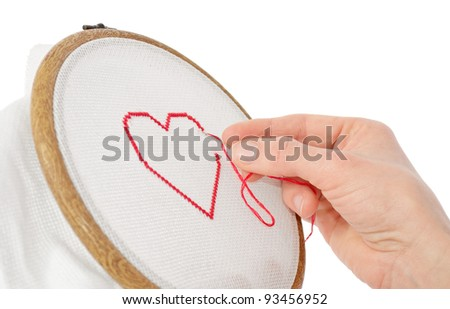 valentine concept: red heart being embroidered - stock photo