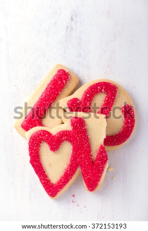Valentine cookie written love on it with sugar icing, broken and isolated over white background, top view, vertical - stock photo