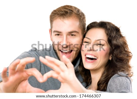 Valentine Couple isolated on white background. Portrait of Smiling Beauty Girl and her Handsome Boyfriend making shape of Heart by their Hands. Happy Joyful Family. Heart Sign. Valentines Day  - stock photo