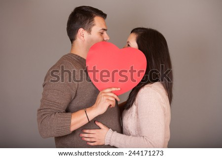 Valentine couple - Portrait of a beautiful smiling girl and her boyfriend kissing behind paper shape of heart, happy valentine couple, heart sign, Valentines Day - stock photo