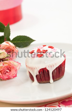 Valentine day chocolate cupcakes garnished with heart shaped sprinkles. Pink roses and gift in background. - stock photo