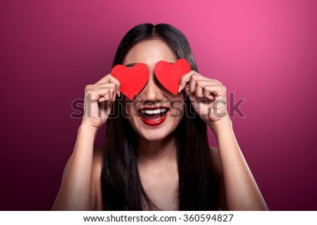 Valentine day concept. Beautiful asian girl holding red heart cover her eyes. - stock photo