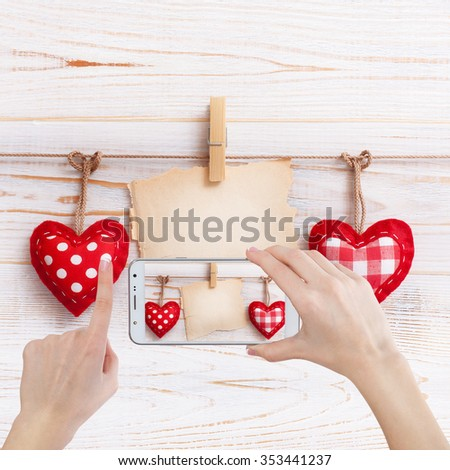 Valentine day love beautiful. Woman taking photo with smart phone. Heart handmade and paper old mark hanging on rope on wooden background. - stock photo