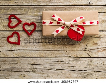 valentine gift box and red heart shapes on wooden board - stock photo