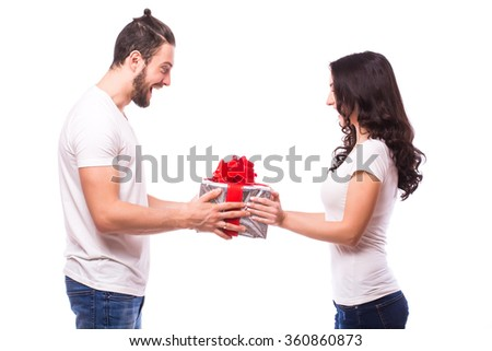Valentine gift. Happy young couple with Valentine's Day present isolated on a white background. Happy man giving a gift to his girlfriend hand to hand. He look at present. Holiday - stock photo