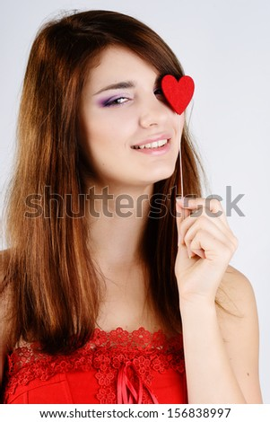 valentine girl with red heart near the eye - stock photo