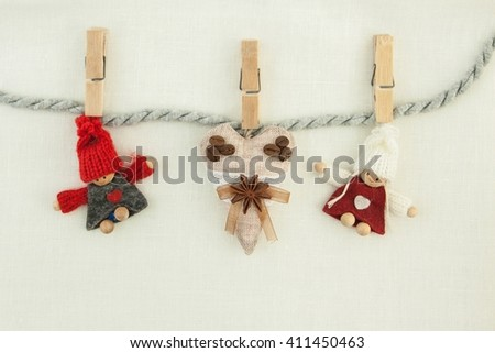valentine, greeting card. Wooden pins, coffee brown heart, knitted loving couple man and woman hanging on a clothesline. On the cloth background - stock photo