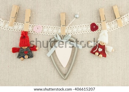 valentine, greeting card. Wooden pins, red and pink hearts, knitted loving couple man and woman, yours lettering on the heart. On the textile background. - stock photo