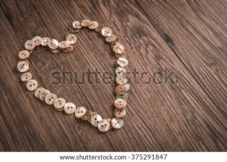 Valentine heart buttons textiles over rustic wooden texture. Top view with copy space. - stock photo