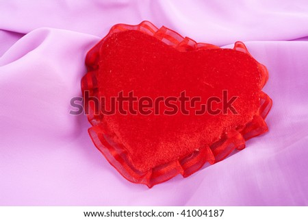 Valentine heart - soft pillow. Valentine's Day heart shaped pillow. Fluffy soft red heart over pink satin. - stock photo