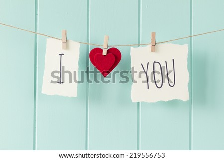 "Valentine. ""I love you"" hanging on a rope with clothespins. A robin egg blue wainscot as background. Vintage Style. - stock photo"