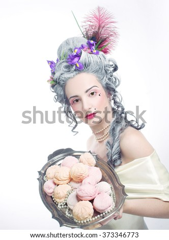 Valentine in victorian style. Young woman in eighteenth century image posing with sweets. - stock photo