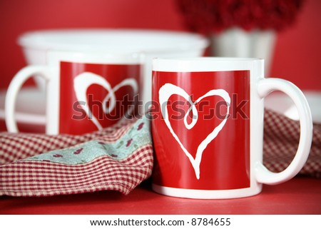 Valentine Morning: The table is set for a romantic breakfast for two. Two red and white heart mugs with dishware and roses in the background. - stock photo