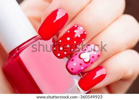 Valentine Nail art manicure. Valentines Day Holiday style bright Manicure with painted hearts and polka dots. Bottle of Nail Polish. Beauty salon. Hand. Trendy Stylish Colorful Nails, Nailpolish - stock photo