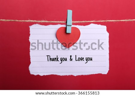 Valentine note paper with red heart and Thank you Love you text hanging on line against red background. - stock photo