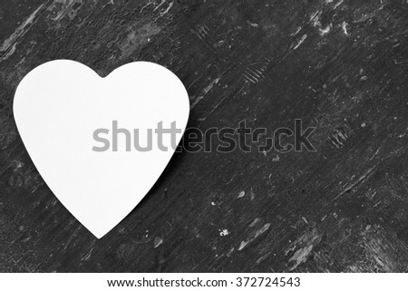 Valentine - paper white heart against a black wooden background. Copy space. Free space for text, Close-up, top view, Black and white photo - stock photo