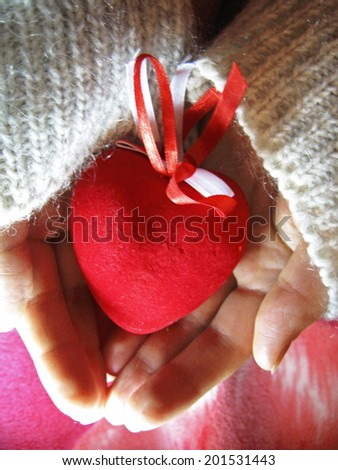 Valentine red heart in woman tender hands - stock photo