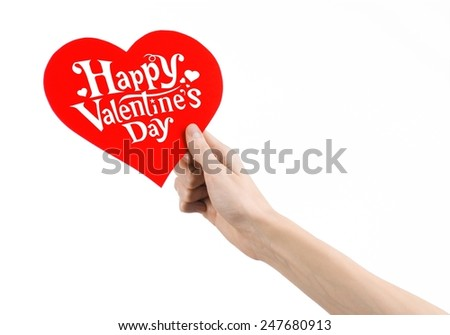 Valentine's Day and love theme: hand holds a greeting card in the form of a red heart with the words Happy Valentine's day isolated on white background in studio - stock photo