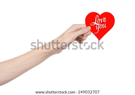 Valentine's Day and love theme: hand holds a greeting card in the form of a red heart with the words Love you isolated on white background in studio - stock photo