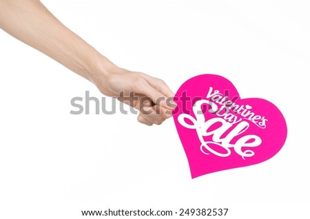 Valentine's Day and sale topic: Hand holding a card in the form of a pink heart with the word Sale isolated on white background in studio - stock photo