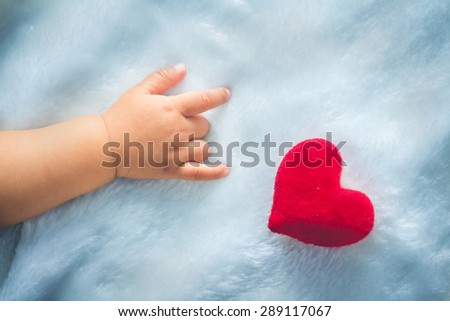 Valentine's Day - baby hands with red Heart - stock photo