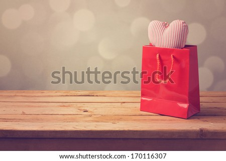 Valentine's day background with shopping bag and heart shape - stock photo
