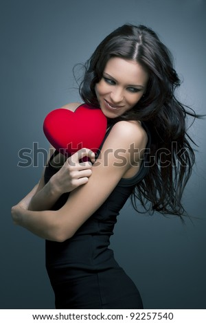 Valentine's Day. Beautiful smiling woman with a gift in the form of heart in his hands - stock photo