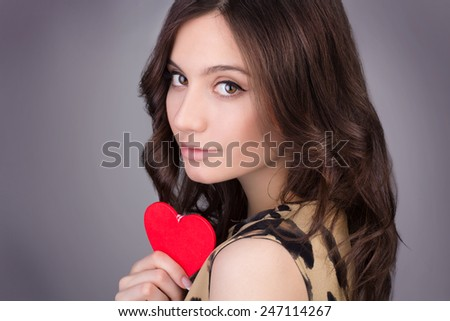 Valentine's Day. Beautiful woman with hearts in her hands. Young woman with red hearts on grey background. portrait of attractive smiling woman isolated on grey studio shot with hearts - stock photo