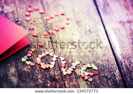 """Valentine's day card with small hearts on wooden background and word """"LOVE""""/ romantic love background - stock photo"""