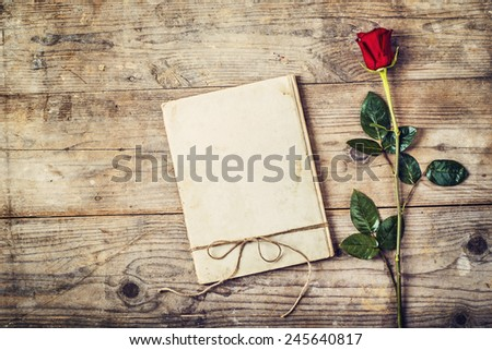 Valentine�´s day composition of a love journal and a red rose. Studio shot on a wooden floor background. - stock photo
