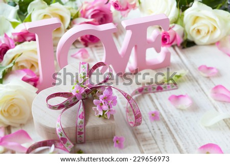 "Valentine's day concept with gift box, letters ""love"" and flowers on old vintage wooden background - stock photo"
