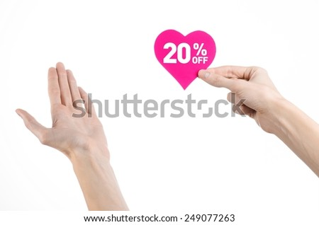 Valentine's Day discounts topic: Hand holding a card in the form of a pink heart with a discount of 20% on an isolated white background in studio - stock photo