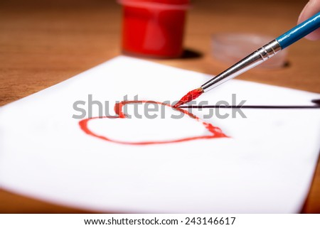 Valentine's Day drawing. woman's hand with a brush paints a heart - stock photo