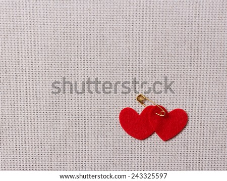 Valentine's day felt red hearts on the burlap with safety pin - stock photo