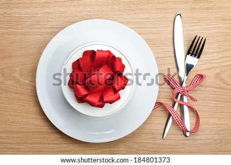 Valentine's day gift box on plate and silverware. View from above on wooden table background - stock photo