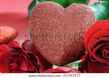 Valentine's Day heart surrounded by red long stem roses. Extreme shallow depth of field with selective focus on heart. - stock photo