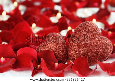 Valentine's Day hearts surrounded by rose petals and lite candles against a white background. Room for copy space with extreme shallow depth of field. - stock photo