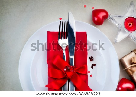 Valentine's Day Romantic Dinner table setting. Date. St. Valentine table served, decorated with bright red hearts, satin ribbon and candles - stock photo