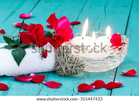 Valentine's Day spa composition with red flowers and rose petals, white towel, rope heart and aroma bowl with three white floating candles on antique rustic teal blue wood background - stock photo