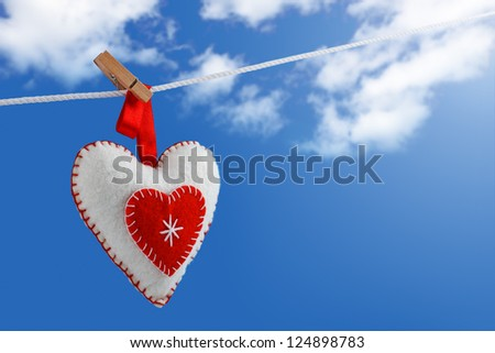 Valentine's day. Woolen heart drying on a rope against blue sky with clouds - stock photo