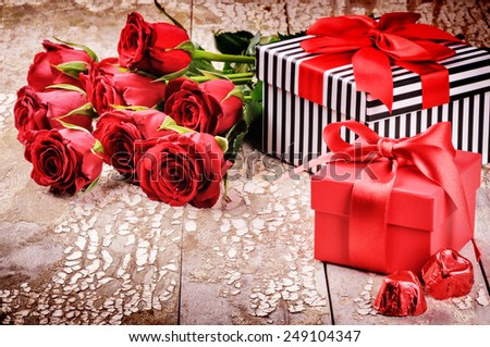 Valentine's setting with bouquet of red roses and presents in boxes - stock photo