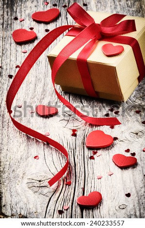 Valentine's setting with gift box and red hearts decorations - stock photo