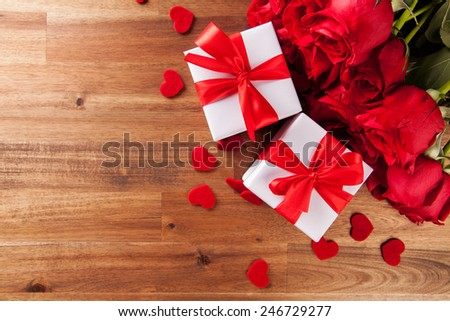 Valentines concept with bouquet of roses and wrapped gift on wooden table - stock photo