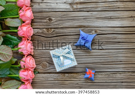 Valentines Day background bordered by roses row on side with little gift boxs and copy space over weathered wood - stock photo