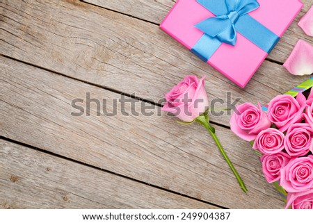 Valentines day background with gift box full of pink roses over wooden table. Top view with copy space - stock photo